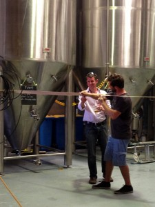 Mike Baird cuts a large ribbon across the front of brewery tanks