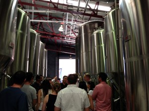 A group of people between rows of tall brewing tanks.