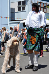 Costumed roving entertainers dress as a large dog and a giast Scotts man