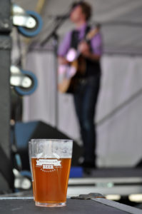 A cup of GABF beer on stage with an out of focus Bob Evans in the background
