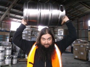 Sean Ryan holds a keg above his head at a brewery