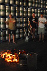 Brewery owners, Jamie, Brad and Ross, standing in front of the fire of rocks.
